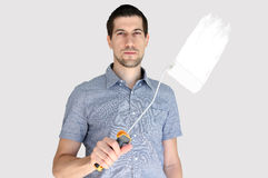 Attractive casual young man holding a paint brush. A portrait of attractive casual young man holding a paint brush Stock Photos