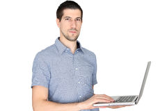 Attractive casual young man using laptop. A portrait of attractive casual young man using laptop Royalty Free Stock Photo