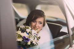 Attractive caucasian bride in wedding car smiling looking through the window Royalty Free Stock Image