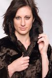 Attractive Caucasian brunette. Attractive young Caucasian brunette wearing a fake fur coat Royalty Free Stock Photos