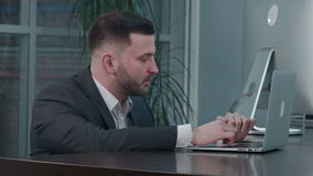 Attractive caucasian businessman using laptop, while talking with partner at workplace. Close up. Professional shot in 4K resolution. 085. You can use it e.g stock video footage