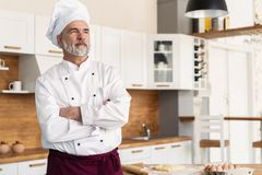 Attractive Caucasian chef standing with arms crossed in a restaurant kitchen stock images