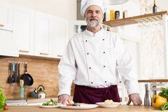Attractive Caucasian chef standing in a restaurant kitchen stock photos