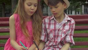 Children draw in the album together on the bench. Attractive caucasian children drawing in the album together on the bench. Close up of little blond girl helping stock footage