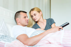 Attractive caucasian couple in bed. Man watching tv, woman lovingly looking at him, hoping to catch his attention. Young attractive caucasian couple in bed. Man Royalty Free Stock Photos