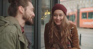 Attractive caucasian couple on a date in a city. Beautiful couple sitting in outdoors restaurant stock video footage
