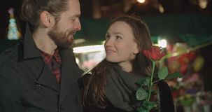 Attractive caucasian couple on a date in a city at night. Young beautiful couple standing on city street at night. Young man and his girlfriend with red rose on stock video footage
