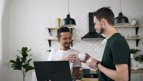 Attractive caucasian couple gay men are drinking coffee and working on laptop computer at home kitchen. Concept of gay. Men life. Slow motion stock video