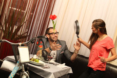 An attractive caucasian couple having a meal with wine at restaurant with a bike Stock Photo