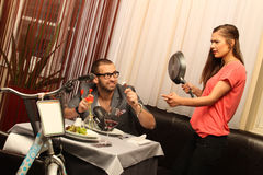 An attractive caucasian couple having a meal with wine at restaurant with a bike Stock Photography