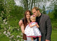 Attractive Caucasian Family. This attractive Caucasian family are a mom and dad and a baby girl.  Dad is kissing baby while arm is around mom Stock Images