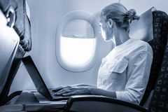 Attractive caucasian female passenger looking through the plain window while working on modern laptop computer using stock images