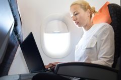 Attractive caucasian female passenger working at modern laptop computer using wireless connection on board of commercial stock photos