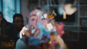 Attractive Caucasian girl blows out confetti. Slow motion. Excited happy woman blowing glitter on a party, smiling. stock footage