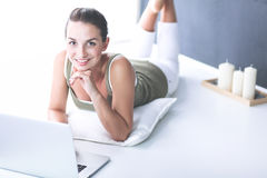 Attractive caucasian girl lying on floor with laptop Stock Photo