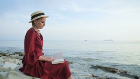 An attractive Caucasian girl in a red bright dress and a straw hat sits on a large stone by the sea at sunset and reads. An interesting book on the sea horizon stock footage