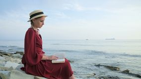 An attractive Caucasian girl in a red bright dress and a straw hat sits on a large stone by the sea at sunset and reads. An interesting book on the sea horizon stock video footage