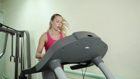 Attractive caucasian girl running on the treadmill in the sport gym. Beautiful fit young woman in a gym doing exercises on a running track stock video