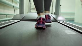 Attractive caucasian girl running on the treadmill in the sport gym. feet close-up. Beautiful blonde in a gym doing exercises on a treadmill. The girl runs stock video footage