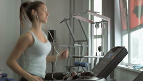 Attractive caucasian girl running on the treadmill in the sport gym with phone and earphones. Beautiful girl running on a treadmill in the gym stock video