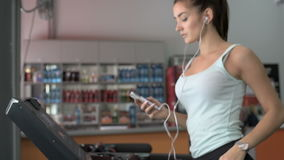 Attractive caucasian girl running on the treadmill in the sport gym with phone and earphones. Beautiful girl running on a treadmill in the gym stock video footage