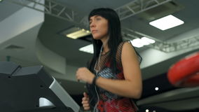 Attractive caucasian girl running on the treadmill in the sport gym with phone and earphones. stock video