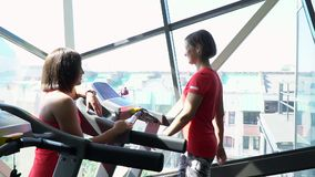 Attractive caucasian girl running on the treadmill in the sport gym stock footage