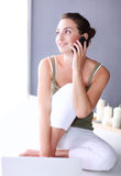 Attractive caucasian girl sitting on floor with phone Stock Image