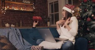 Attractive Caucasian Girl Sitting near Christmas Tree Using Her Laptop Thinks and Orders Present. Gift Box Appears in