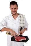Attractive caucasian male cook preparing steak. Young attractive caucasian male cook with uniform preparing a tender t-bone steak for grill. Studio shot. White royalty free stock image