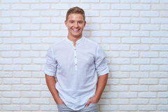 Attractive Caucasian man leaning on a white brick wall and holdi Royalty Free Stock Image
