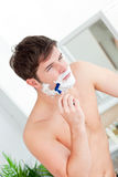 Attractive caucasian man shaving in the bathroom Royalty Free Stock Photos