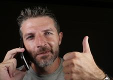 Attractive Caucasian man talking on mobile phone having business conversation isolated on black background giving thumb up in royalty free stock images