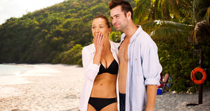 Attractive Caucasian millennial couple standing at the beach people watching Stock Photos