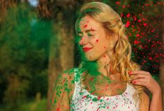 Attractive caucasian model with long wavy hair posing with color. Attractive caucasian woman with long wavy hair posing with color splash of a dry Holi paint royalty free stock images