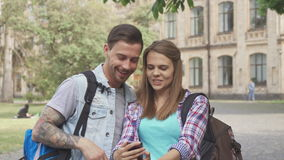 Students take selfies on campus. Attractive caucasian students taking selfies on campus. Cute young people using some smartphone app to make funny effects on stock video