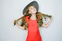 Attractive caucasian teen girl in red dress and hat looking up dreamily. Beautiful blonde with green dyed hair tips royalty free stock images