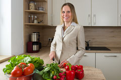 Attractive Caucasian woman in business suite cutting vegetables Royalty Free Stock Image