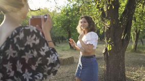 Attractive caucasian woman with curly hair posing in background while her friend taking a photo using old camera in. Attractive caucasian woman with curly hair stock video footage