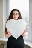Attractive caucasian woman holding a baloon heart.  Stock Photos