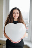 Attractive caucasian woman holding a baloon heart.  Royalty Free Stock Photography