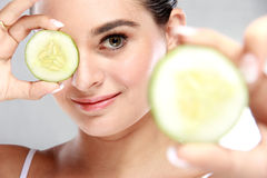 Attractive caucasian woman holding and showing slices of cucumbe Royalty Free Stock Image