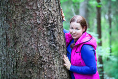 Attractive Caucasian woman hugging a big pine tree trunk Royalty Free Stock Images