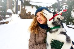 Attractive caucasian woman hugs funny malamute dog wearing santa dear christmas antlers. Curly smiling female having fun. With huskie puppy on new year. Pet is royalty free stock images