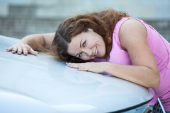 Attractive Caucasian woman laying her cheek on car bonnet Royalty Free Stock Image