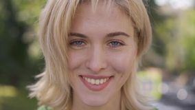 Attractive caucasian woman with medium length haircut looking at camera. Portrait of a beautiful blonde grey-eyed girl. Attractive caucasian woman with medium stock video