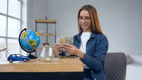 Attractive caucasian woman opening glass jar with money. stock video