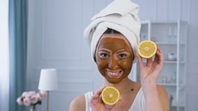 Attractive caucasian woman posing with two half of lemon with brown mask on the face. stock video