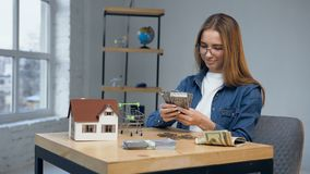 Attractive caucasian woman counting money. Attractive caucasian woman in stylish glasses counting money for buying house of dream stock video
