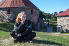 Attractive Caucasian woman wearing motorcycle outfit sitting on green meadow in some landmark attraction, copy space Stock Photos